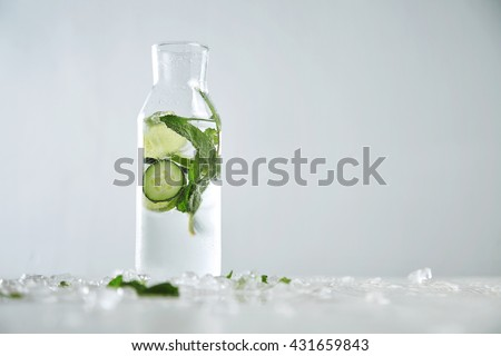 Vintage glass bottle filled with cold fresh cucumber mint lime lemonade like mojito witount alcohol, ideal drink for summer isolated on table with melted ice - stock photo