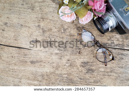 Vintage glasses and camera on wooden background. Copy space for your text - stock photo