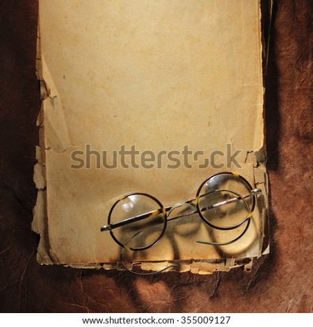 Vintage glasses on the very old paper - stock photo
