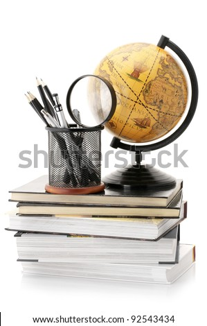 Vintage globe on stack of books and office supplies isolated against white background. - stock photo