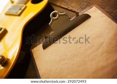 Vintage gold top single cutaway guitar on old wood surface and old clipboard, good for playlists, and production notes. Shallow depth of field. - stock photo