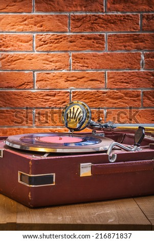 vintage gramophone on table and background of brickwall - stock photo