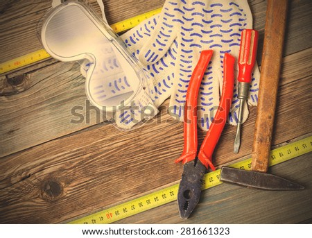 vintage hammer, old pliers, screwdriver, tape measure, gloves and safety glasses on aged  textured boards bench. still life with working tools. instagram image filter retro style - stock photo