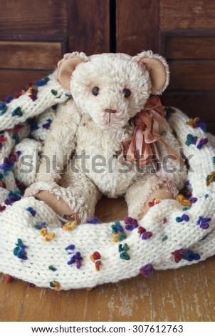 Vintage handmade Teddy Bear wrapped in a scarf. - stock photo