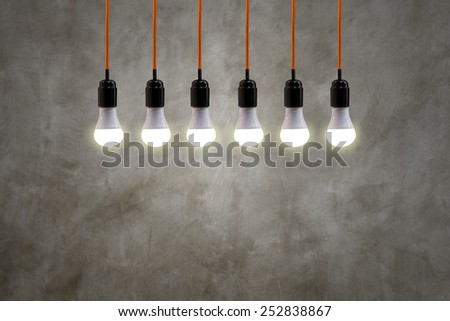 vintage hanging energy light bulbs on concrete retro, background - stock photo