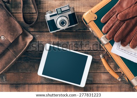 Vintage hipster traveler packing ready to leave with camera and digital touch screen tablet, top view - stock photo
