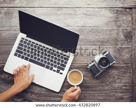 Vintage hipster wooden desktop top view, hands using a laptop and holding a cup of coffee, Instant photo vintage split toning color effect.  - stock photo