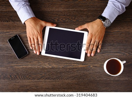 Vintage hipster wooden desktop top view, male hands using a laptop and holding a cup of coffee - stock photo