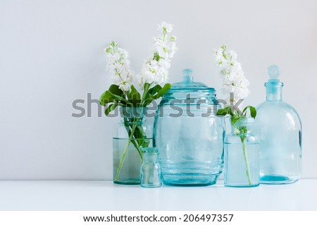 Vintage home decor background, white matthiola flowers in different blue glass bottles vases and antique jars on a shelf by the wall - stock photo