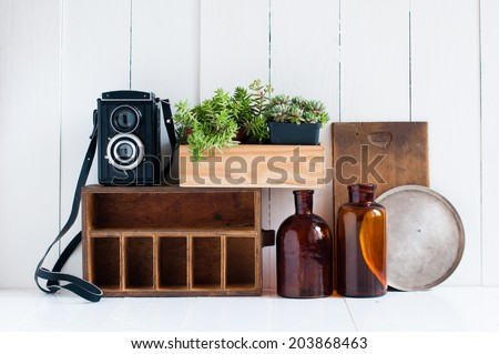 Vintage home decor: old wooden boxes, houseplants, camera and old brown glass bottles on white wooden board, retro home interior. - stock photo