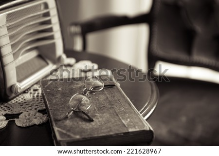 Vintage home interior with old radio and book on round wooden table. - stock photo