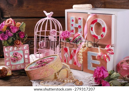 vintage home still life with wooden drawers box,pink cage and photo frame in romantic style   - stock photo