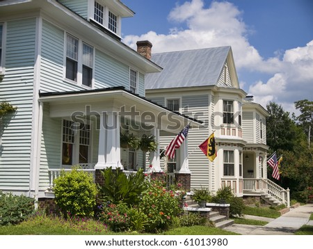 Vintage homes in New Bern North Carolina flying the American Flags and the flags of the town of New Bern. - stock photo