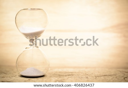 Vintage hourglass on wooden background with copy space,Focus on the middle of hourglass - stock photo