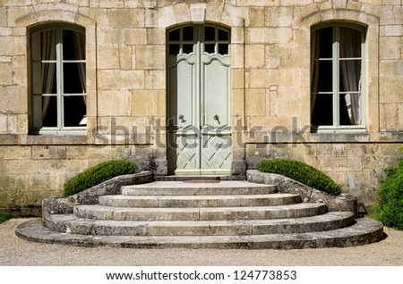 Vintage house wall with entrance staircase, door and windows - stock photo
