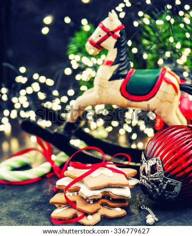 Vintage hristmas decoration, rocking horse and gingerbread cookies. retro style toned picture. Selective focus - stock photo