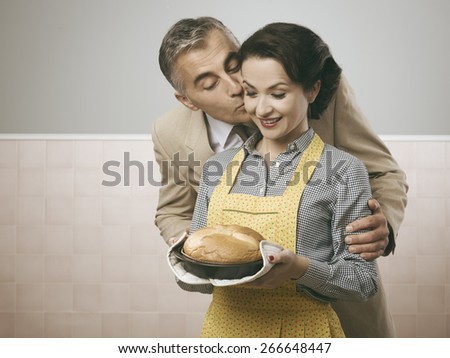 Vintage husband kissing her wife, she is holding a delicious home made cake - stock photo