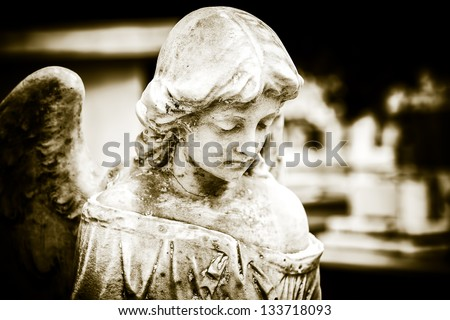 Vintage image of a sad angel on a cemetery with a diffused background - stock photo