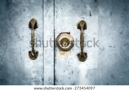 Vintage image of key hole and door handle on grunge door - stock photo