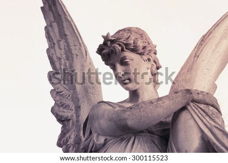 Vintage image of sad angel on a cemetery against the white background (details) - stock photo