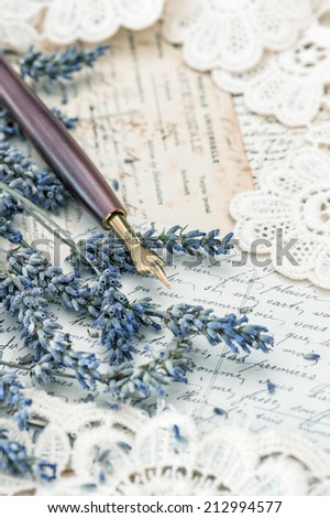 vintage ink pen, dried lavender flowers and old love letters. retro style toned picture. selective focus - stock photo