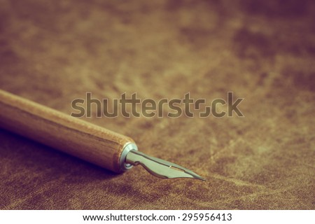 Vintage ink pen on leather background - stock photo