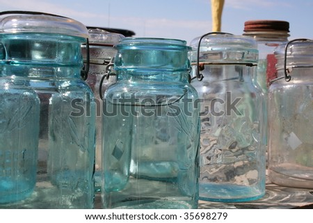 Vintage jars lined up on a table - stock photo