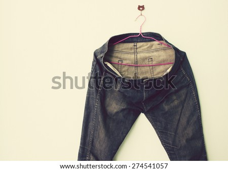 Vintage,Jeans hanging on the wall - stock photo