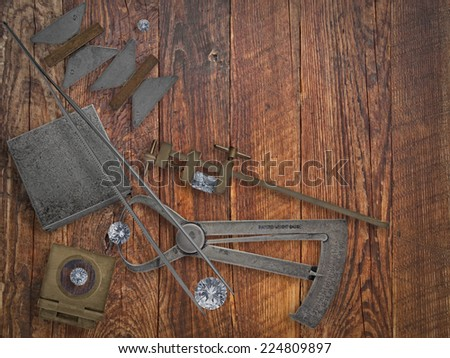 vintage jeweler tools and diamonds over wooden bench, space for text - stock photo