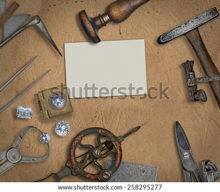 vintage jeweler tools and diamonds over  working bench, blank business card for your text - stock photo