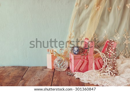 vintage jewelery, antique wooden jewelry box and perfume bottle on wooden table.  - stock photo