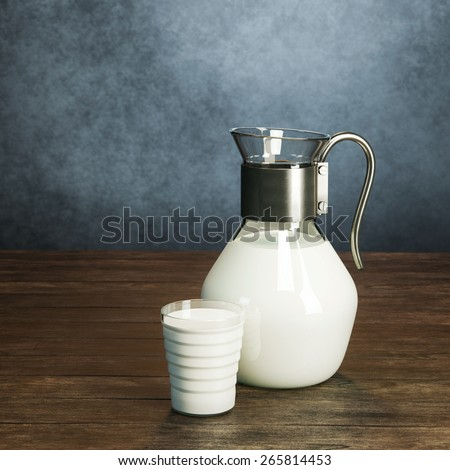 Vintage jug full of milk and glass on the wooden table behind grey wall background  - stock photo