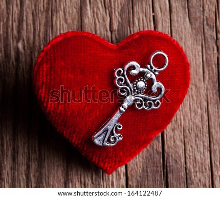 vintage key and red heart on wooden background - stock photo
