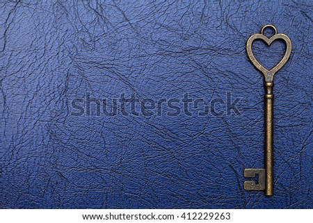 vintage key heart shape on a blue leather background - stock photo