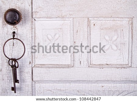 Vintage key unlocking an  old cracked antique or vintage door - stock photo