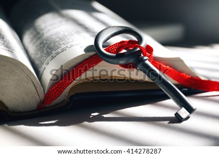 Vintage key with red rope bookmark on a light table. - stock photo