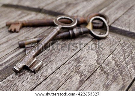Vintage keys on old wooden background. Close-up. Three old, rustic keys on the table.  - stock photo