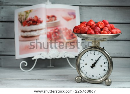 Vintage kitchen scale weighting strawberries on recipe magazine background - Strawberry cake - stock photo
