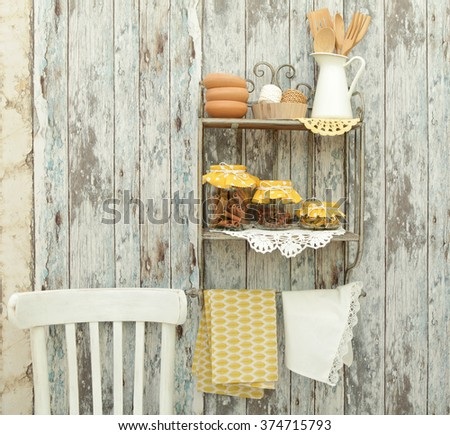 Vintage kitchen utensils and spices(cinnamon,cloves,turmeric) in glass jars on the shelf,rustic chair on a wooden wall - stock photo