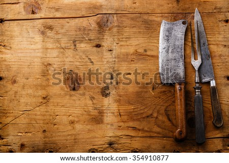 Vintage kitchenware kitchen utensils Meat Fork and Butcher Cleaver on wooden background - stock photo