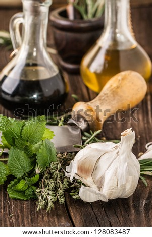 vintage knife with garlic, mint and thyme, oil and vinegar in vintage bottles on old wooden table - stock photo