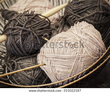 Vintage knitting needles and yarn inside old wire basket, still life photo with soft focus - stock photo
