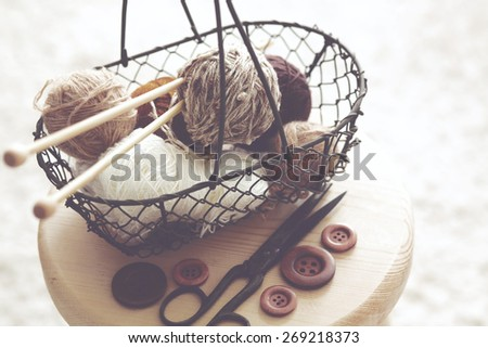 Vintage knitting needles, scissors and yarn inside old wire basket on wooden stool, still life photo with soft focus - stock photo