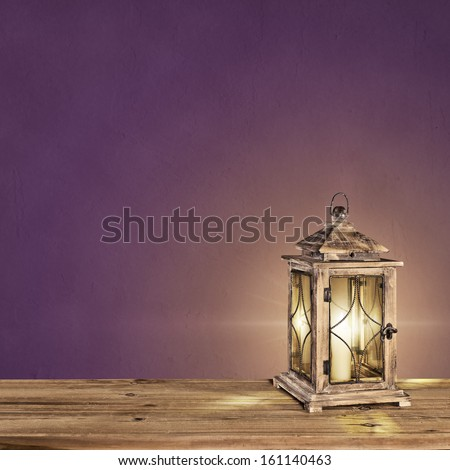 vintage lantern with a candle on a violet vintage background - stock photo