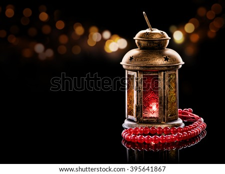 Vintage lantern with red rosary. Ramadan mood at night with light decoration in the background. - stock photo