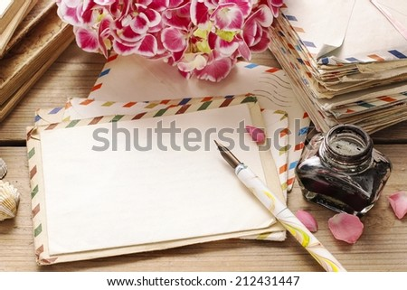 Vintage letters, ink and pen. Bouquet of pink hortensia (hydrangea) flowers in the background - stock photo