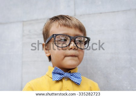 vintage little boy with a bow tie and glasses - stock photo