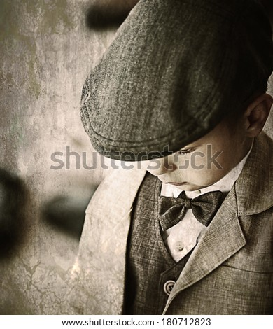 Vintage little cute kid wearing retro suit and cap - stock photo