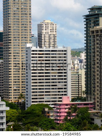 Vintage little pink hotel among the towering giants just off Waikiki Beach in Honolulu - stock photo