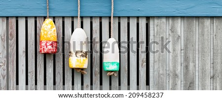 Vintage lobster buoys against a weathered wood fence. Banner format with copy space. - stock photo